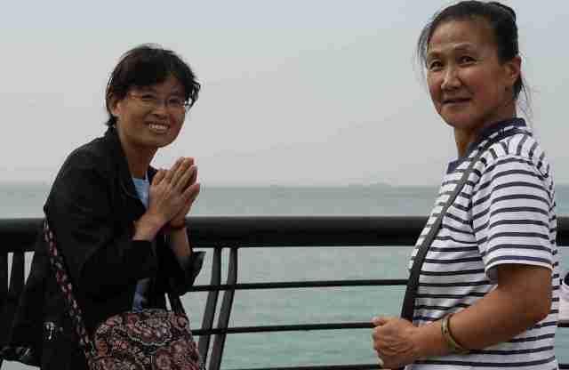 Women praying before throwing shellfish into sea